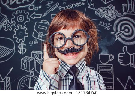 Little boy as businessman or teacher with mustache and glasses standing on dark background pattern. Wearing shirt, tie. Lifting a finger up