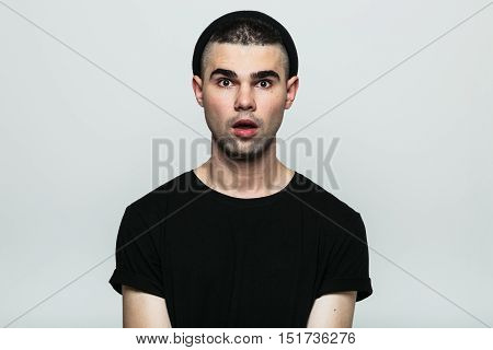 Isolated portrait of emotional shocked man wearing black t-shirt and hat with opened mouth. Front view. Studio shot on gray background.