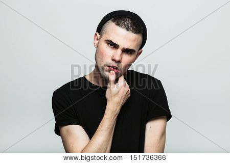 Studio portrait of sensual and thinking man looking at camera posing with hand on chin.