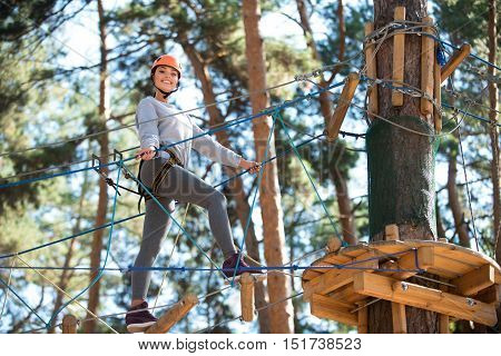 Almost here. Energetic happy young woman keeping balance and making a step forwards while getting to the tree