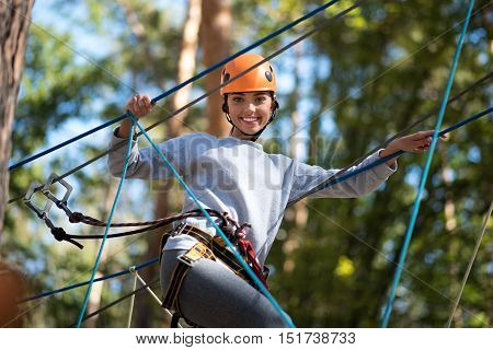Need to be cautious. Positive confident careful woman wearing a mountaineering helmet and special safety equipment while following the ropes road