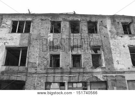 Black and white photo of abandoned destroyed damaged rundown old apartment house building facade with broken glass windows. Renovation, construction, building, architecture, exterior concept Close up brick wall texture detail