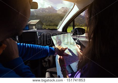 traveler girl sitting in the car looking map. Dolomites Italy.