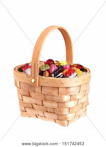 Basket filled with asorted candy isolated on white background