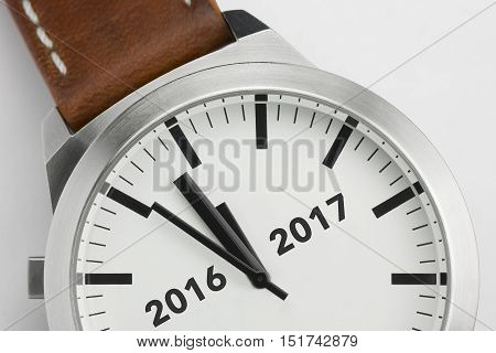 Traditional watch with analog conceptual visualization of the turn of the year from two thousand sixteen to two thousand seventeen