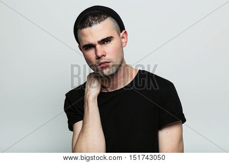 Studio portrait of serious man wearing black t-shirt looking at camera with hand on neck.