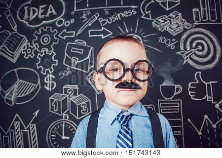 Little boy as businessman or teacher with mustache and glasses standing on dark background pattern. Wearing shirt, tie.