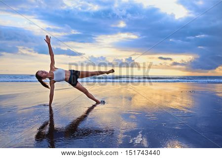 Active sporty woman stand in yoga pose on black sand beach to keep fit and health. Sunset blue ocean surf background with sun. Woman fitness morning workout sport activity on summer family holiday
