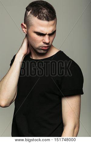 Man on grey studio background scowling at something