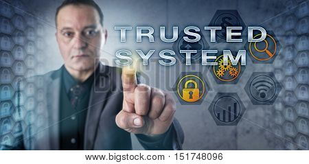 Experienced male security expert is touching TRUSTED SYSTEM on a virtual monitor. Information technology metaphor and security engineering concept for a system capable of enforcing a security policy.