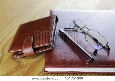 pen business wallet glasses and notebook on wooden table