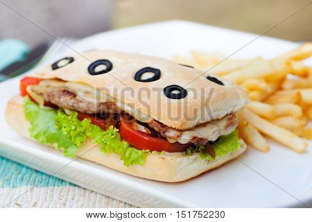 Ciabatta sandwich with grilled beef, tomatoes, cheese and lettuce with french fries on white plate Summer background