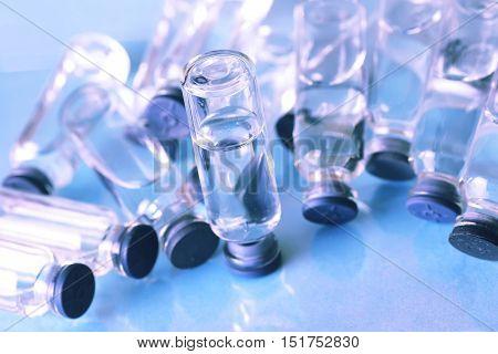 transparent vials of medicine on blue background