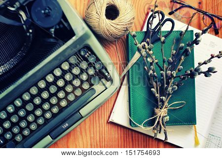 spring willow and typewriter on a wooden background