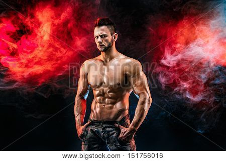 Close up on perfect abs. Strong bodybuilder with six pack. Man with perfect abs, shoulders, biceps, triceps and chest, personal fitness trainer flexing his muscles in blue, red smoke