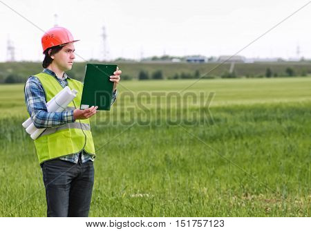 man with cottage plan construction in green field