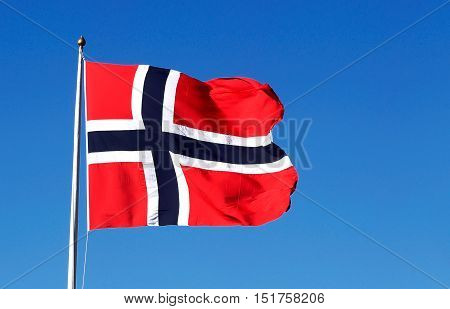 The national flag of Norway isolated on blue sky.