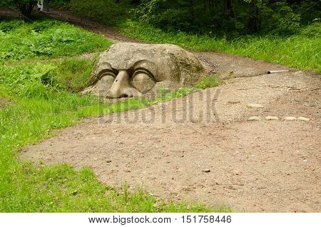 Forest path with gravel come to a stone head.