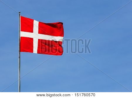 The red and white flag of Denmark on blue sky.