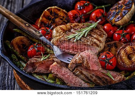 Steak with grilled vegetables in a frying pan selective focus.