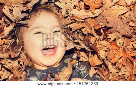 Happy Toddler Girl Smiling While Lying Down In A Pile Of Leaves