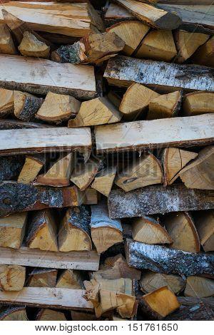 Chopped hardwood firewood stacked piles. Logsa lot