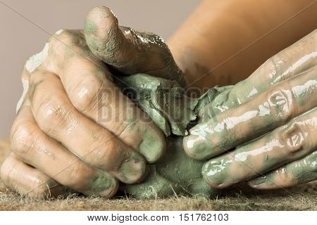 hands of woman kneading raw blue clay