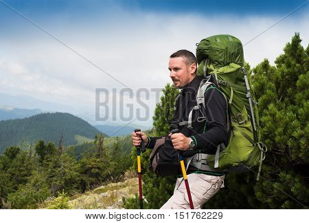 Tired hiker relaxes with a large backpack on a in the mountains.Young hiker with backpack resting on a rocky hill. The man got tired at lifting on mountain.