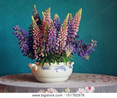 Still-life with a bouquet of lupine on the table with a tablecloth on a retro blue background.