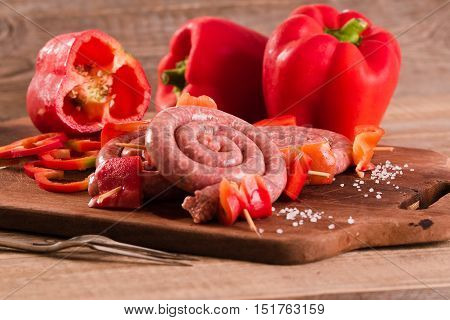Raw sausage with bell pepper on wooden table.