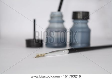 Ink bottles and brush isolated on the white background