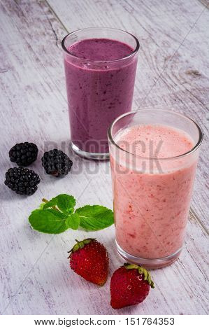 smoothie of strawberries and blackberry strawberries blackberry and mint leaves on a white wooden table