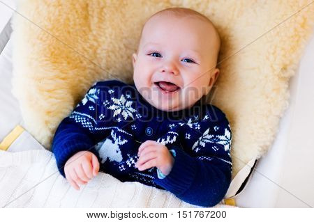 Funny little baby relaxing in a bouncer with sheepskin foot muff wearing warm knitted reindeer Christmas sweater at home on cold winter day. New born boy in stroller. Newborn child in rocking chair.