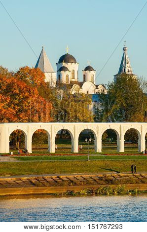 Architecture landscape - arcade of Yaroslav Courtyard and ancient St Nicholas cathedral with towers at autumn sunset with people walking along in Veliky Novgorod Russia