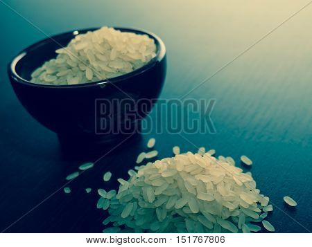 A bowl of uncooked raw risotto rice with a vintage blue style