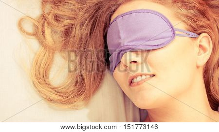 Tired woman sleeping in bed wearing blindfold sleep mask. Young girl taking nap. Instagram filtered.