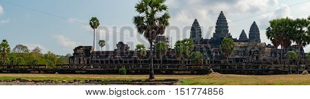 Panoramic view of ancient ruins of temple complex Angkor Wat seen across the pond with lilies Siem Reap Cambodia.