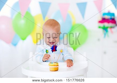 Adorable baby boy celebrating first birthday blowing candles on colorful cup cake. Kids birthday party decorated with balloons and pastel color banner. Child eating cake and candy.
