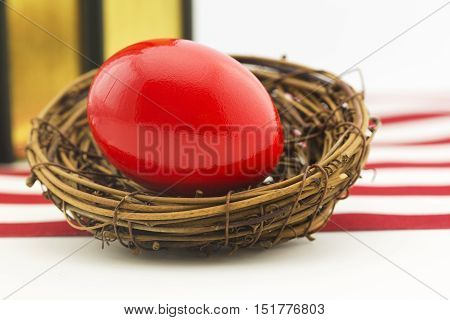 Red nest egg in front of books and red and white stripes of American flag.