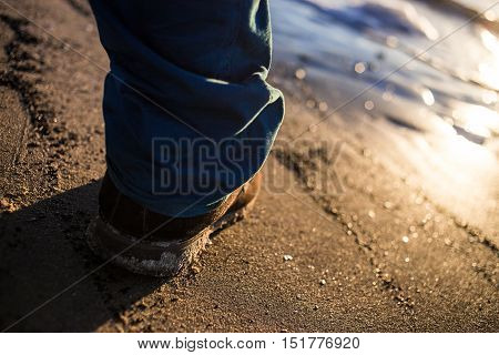 Male shoes on textured sea sand contrast blue trousers.