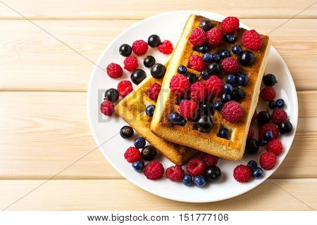 Soft waffle with fresh blueberry and raspberry top view. Breakfast soft waffles with fresh seasonal berries