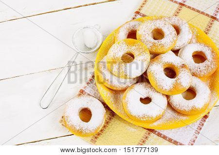 Donuts with caster sugar served on yellow plate top view copy space. Sweet dessert pastry doughnuts. Hanukkah sweet donuts.
