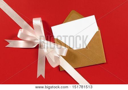 White Gift Ribbon And Bow Diagonal On Red Paper Background With Brown Envelope And Blank Card