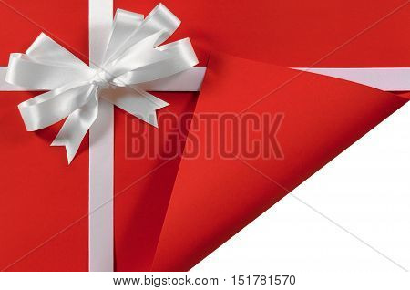 Christmas Or Birthday White Satin Gift Ribbon And Bow On Red Paper Background With Open Folded Corne