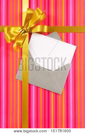 Christmas Or Birthday Card With Gift Ribbon And Bow In Gold Satin On Pink Candy Stripe Paper Backgro