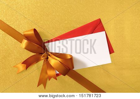 Christmas Or Birthday Card With Gift Ribbon And Bow In Gold Satin On Shiny Paper Background With Red