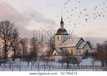 Old Swedish countryside church durig winter season at dusk with a group of birds in the sky.