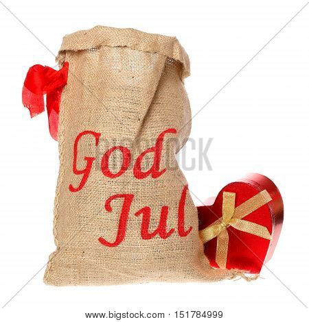 The text Merry Christmas in Swedish on a sac with a red heart-shaped box near by isolated on white background..