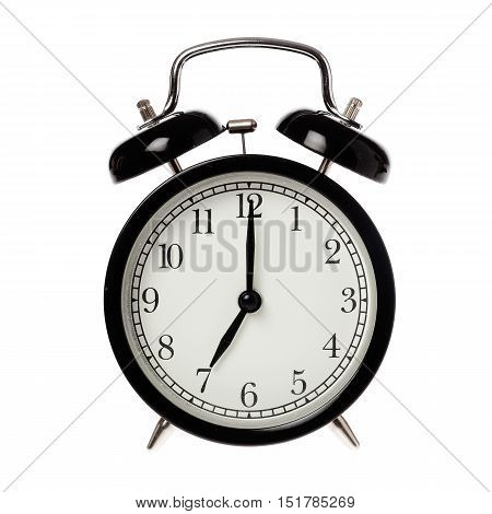 Back alarm clock with analog display seven o clock isolated on white.