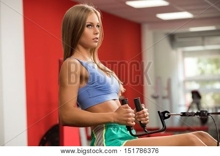 Fitness. Beautiful girl practicing on simulator in gym